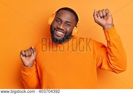 Photo Of Carefree Bearded Man With Dark Skin Thick Beard And Toothy Smile Raises Arms Dances Carefre