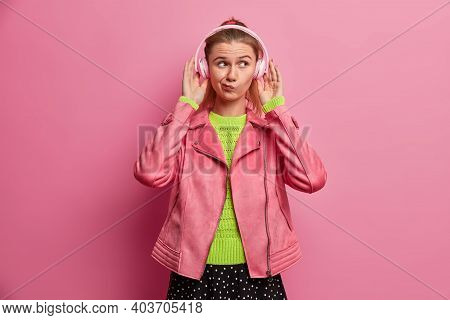 Serious Young Pretty Female Model Smirks Face Concentrated Thoughtfully Aside While Listening Music
