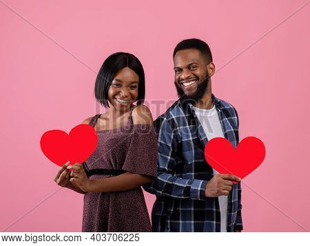 Lovers Holiday. Beautiful Young Black Couple Holding Red Hearts And Looking At Camera On Pink Studio