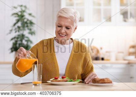 Joyful Senior Woman With Short Grey Hair Having Healthy Lunch At Home, Smiling And Pouring Fresh Ora