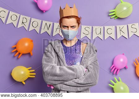Angry Redhead European Woman Looks Annoyed Keeps Arms Folded Wears Disposable Mask To Protect From C