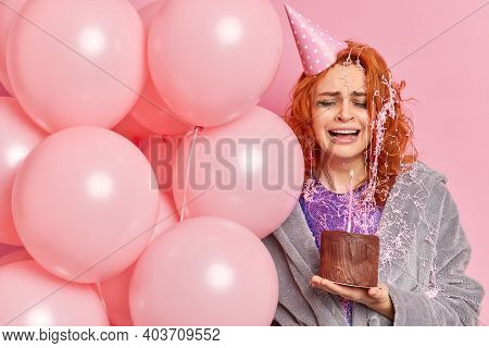 Horizontal Shot Of Dejected Redhead European Woman Crying As Feels Lonely On Birthday Holds Inflated