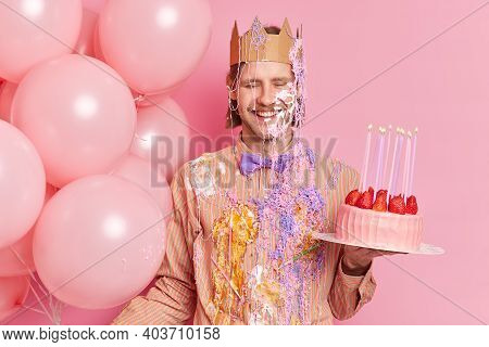 Overjoyed Man Smeared With Cream Has Festive Mood Holds Strawberry Cake And Helium Balloons Celebrat