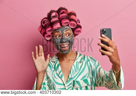 Happy Positive Woman Applies Clay Mask On Face To Rejuvenate Skin Applies Hair Rollers Waves Hello A
