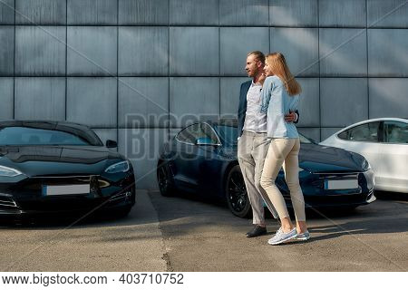 Cheerful Young Caucasian Couple Choosing New Car While Walking Along Row Of Autos Outdoors. Choosing