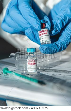 Doctor Or Nurse In Protective Suit Holding Covid 19 Vaccine And