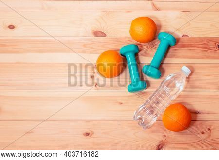Two Green Dumbbells, Bottle Of Water And Oranges On Wooden Background. Fitness And Healthy Eating Co
