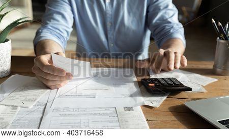 Young Skilled Man Analyzing Utilities Household Bills Or Taxes.