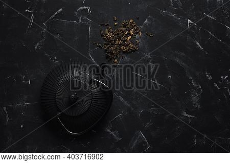 Metal Black Teapot And Dry Tea Leaves On A Black Stone Background. Asian Cast Iron Teapot. Top View,