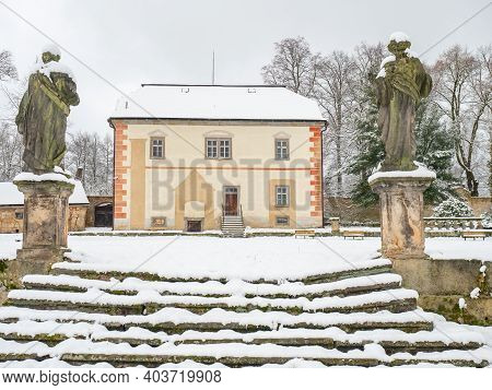 Historical Building In Winter Garden. Old Statues Guard Old Stony Staircase Under Snow Cover.
