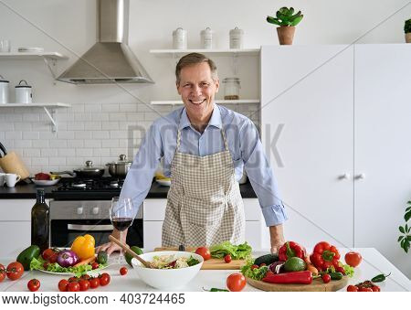 Smiling Happy Senior Mature Older 50s Man Wearing Apron Standing In Kitchen Table, Looking At Camera