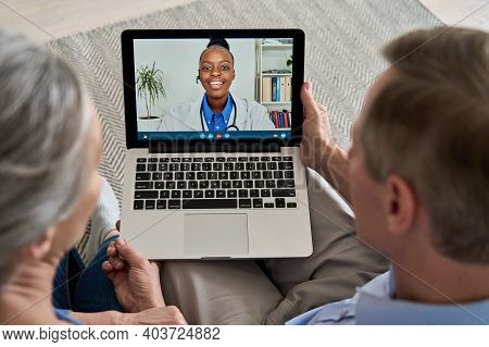 Over Shoulder View Of Old Grandparents Couple Patients Video Calling Virtual Doctor Using Laptop At
