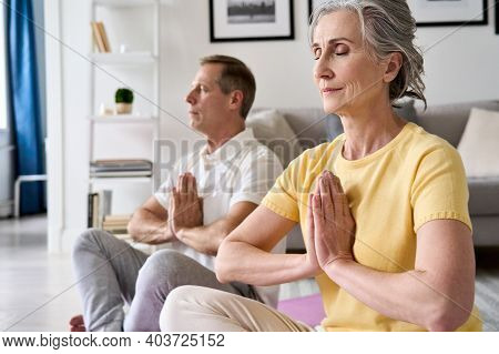 Calm Healthy Serene Old Middle Aged Senior 50s Couple Meditating With Eyes Closed Namaste Hands At H