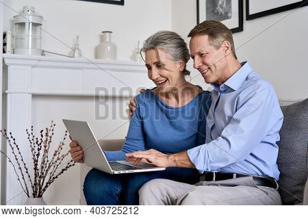 Happy Old Senior Retired Grandparents Using Laptop Sitting On Couch At Home. Smiling Mature 50s Fami
