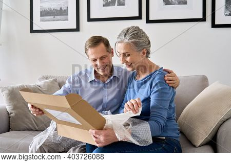 Happy Older Mature Couple Customers Unpacking Parcel Sitting At Home On Couch. Senior Middle Aged Gr