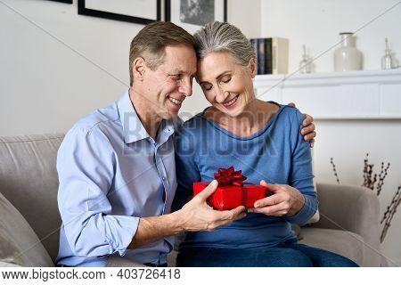 Happy Older Grandparents Celebrating Anniversary At Home. Mature Senior Husband Hugging Smiling Midd