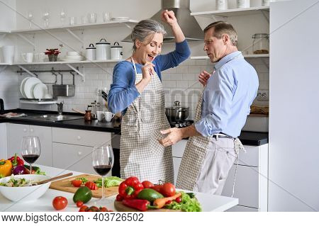 Happy Old Senior 50s Couple Having Fun Dancing Cooking Together In Kitchen. Cheerful Middle Aged Fam