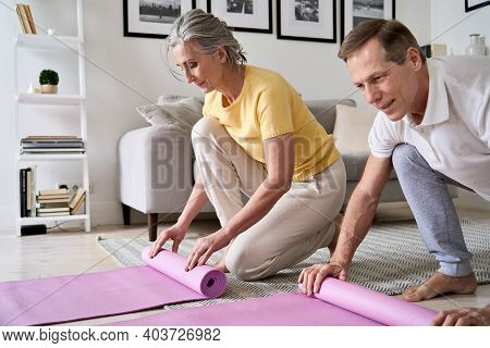 Sporty Fit Middle Aged Old Couple Hands Rolling Or Unrolling Yoga Pilates Mat At Home. Seniors Fitne