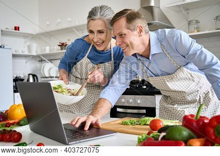 Happy Old Middle Aged 50s Couple Using Laptop Computer Preparing Healthy Food Diet Vegetable Salad A