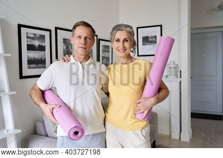Happy Fit Middle Aged Old Couple Hugging, Looking At Camera, Holding Yoga Mats, Standing At Home. Se