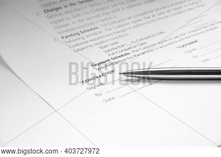 Close-up Of A Silver Pen On Docunent Contract. Legal Contract Signing. Buy Sell Real Estate Contract