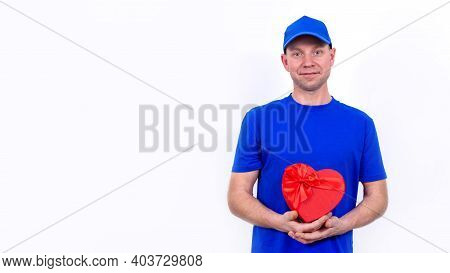 Courier In Blue Uniform Holds A Red Heart-shaped Gift Box For Valentines Day. Home Delivery Of Holid