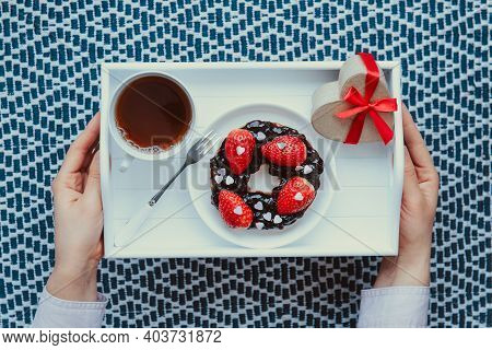Top View Female Hands Holding Romantic Meal For Lover. A Cup Of Tea, Bagel With Jam Decorated With S