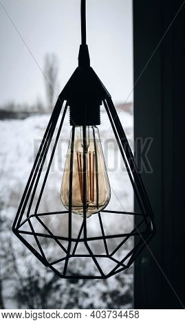 Loft Lamp On The Background Of Winter Outside The Window, Incandescent Lamp, Modern Lamp. Hanging La