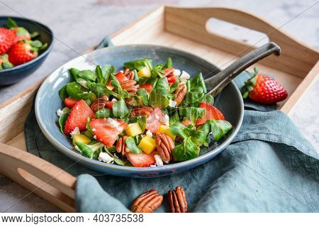 Healthy Lettuce Salad With Mango, Strawberry, Pecan Nuts And Feta Cheese