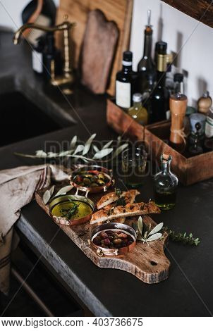 Pickled Greek Olives, Olive Oil In Copper Jars And Herbed Focaccia Slices On Rustic Wooden Board Ove