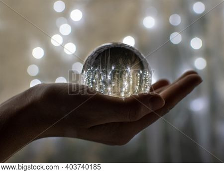 Festive Atmosphere In A Crystal Glass Sphere. Reflections Of Holiday Lights In A Ball Placed On Her