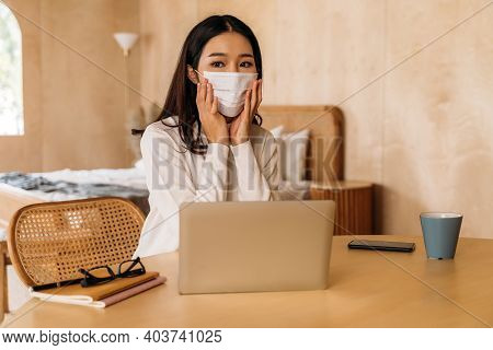 Young Teenage Asian Woman Wears Sweater Using Computer Laptop Working From Home Indoors Online. Attr
