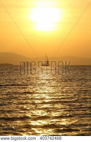 Alone Sailboat At Sunset. Atmospheric Seascape With Orange Sun.