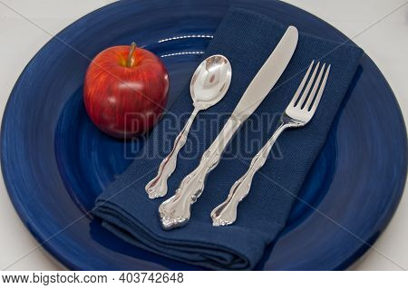 A Place Setting Of Sterling Silver Flatware On A Blue Linen Napkin On A Large, Blue Porcelain Plate