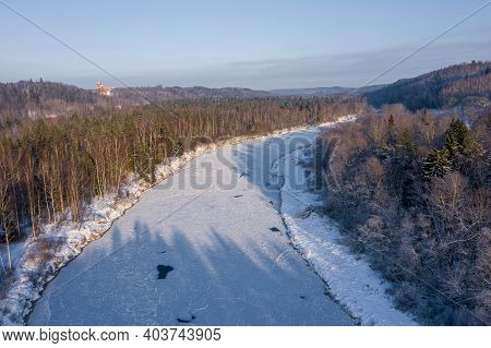 Aerial View Of The River And Snow-covered Forest After A Blizzard In A Morning Haze. Clear Blue Sky.