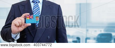 Cropped Image Of Businessman Holding Plastic Credit Card With Printed Flag Of Fiji. Background Blurr