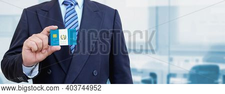 Cropped Image Of Businessman Holding Plastic Credit Card With Printed Flag Of Guatemala. Background