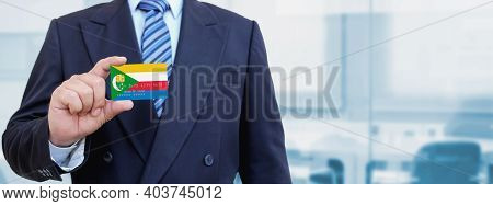 Cropped Image Of Businessman Holding Plastic Credit Card With Printed Flag Of Comoros. Background Bl