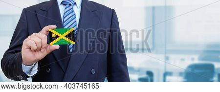 Cropped Image Of Businessman Holding Plastic Credit Card With Printed Flag Of Jamaica. Background Bl