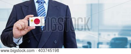 Cropped Image Of Businessman Holding Plastic Credit Card With Printed Flag Of Japan. Background Blur