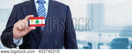 Cropped Image Of Businessman Holding Plastic Credit Card With Printed Flag Of Lebanon. Background Bl