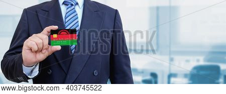 Cropped Image Of Businessman Holding Plastic Credit Card With Printed Flag Of Malawi. Background Blu