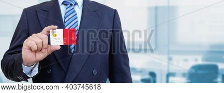 Cropped Image Of Businessman Holding Plastic Credit Card With Printed Flag Of Malta. Background Blur