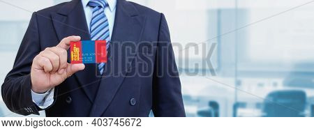 Cropped Image Of Businessman Holding Plastic Credit Card With Printed Flag Of Mongolia. Background B