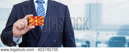 Cropped Image Of Businessman Holding Plastic Credit Card With Printed Flag Of North Macedonia. Backg