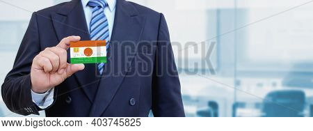 Cropped Image Of Businessman Holding Plastic Credit Card With Printed Flag Of Niger. Background Blur