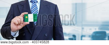 Cropped Image Of Businessman Holding Plastic Credit Card With Printed Flag Of Nigeria. Background Bl