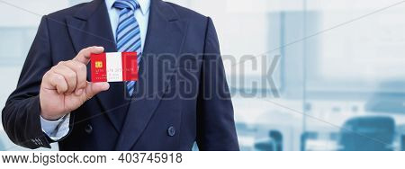 Cropped Image Of Businessman Holding Plastic Credit Card With Printed Flag Of Peru. Background Blurr