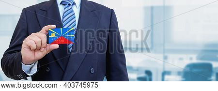 Cropped Image Of Businessman Holding Plastic Credit Card With Printed Flag Of Reunion. Background Bl