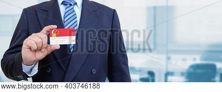 Cropped Image Of Businessman Holding Plastic Credit Card With Printed Flag Of Singapore. Background